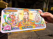 """10 AUGUST 2014 - BANGKOK, THAILAND:     A man holds a stack of Hell Money before tossing it into a burn barrel in Bangkok for Ghost Month. Hell money is a form of joss paper printed to resemble legal tender bank notes and is used in religious ceremonies in Chinese communities. The seventh month of the Chinese Lunar calendar is called """"Ghost Month"""" during which ghosts and spirits, including those of the deceased ancestors, come out from the lower realm. It is common for Chinese people to make merit during the month by burning """"hell money"""" and presenting food to the ghosts.   PHOTO BY JACK KURTZ"""