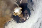 Eruption of Sarychev Peak Volcano, Kuril Islands, north-eastern Japan, 12 June 2009, viewed the International Space Station.  The white matter on the side of the volcano is pyroplastic flow. Credit NASA. Science Geology Vulcanology