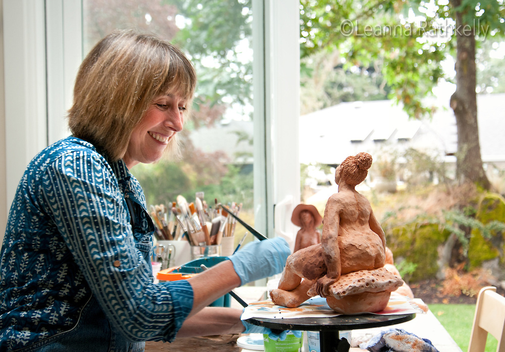 Artist Ginny Glover and her husband David Stuart have renovated a small bungalow in Ten Mile Point and infused it with contemporary style. Here Ginny works on her sculptural figures in her artists' studio, just a short walk away from the main house.