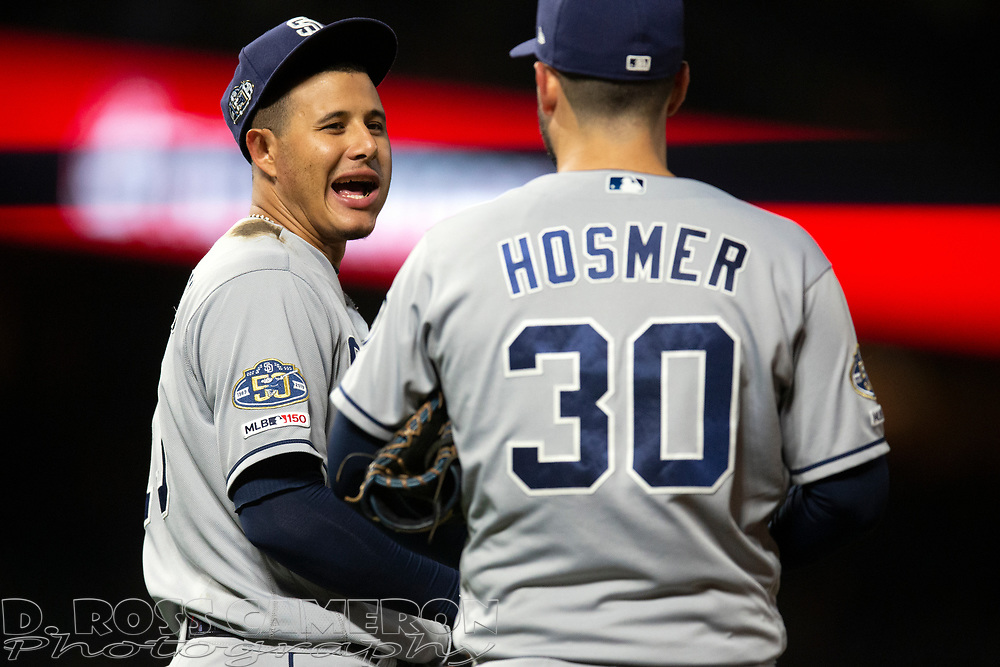 San Diego Padres third baseman Manny Machado (13) and first baseman Eric Hosmer share a laugh between innings of a baseball game against the San Francisco Giants, Thursday, Aug. 29, 2019, in San Francisco. The Padres won 5-3. (AP Photo/D. Ross Cameron)
