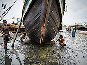 07 NOVEMBER 2014 - SITTWE, RAKHINE, MYANMAR: Workers refurbish a boat in the port of an IDP camp housing Rohingya Muslims near Sittwe. The boats were originally built as fishing boats but are increasingly being used by human traffickers to take people to Malaysia. The government of Myanmar has forced more than 140,000 Rohingya Muslims who used to live in Sittwe, Myanmar, into squalid Internal Displaced Person (IDP) camps. The forced relocation took place in 2012 after sectarian violence devastated Rohingya communities in Sittwe and left hundreds dead. None of the camps have electricity and some have been denied access to regular rations for nine months. Conditions for the Rohingya in the camps have fueled an exodus of Rohingya refugees to Malaysia and Thailand. Tens of thousands have put to sea in rickety boats hoping to land in Malaysia but sometimes landing in Thailand. The exodus has fueled the boat building boom on the waterfront near the camps. Authorities expect the pace of refugees fleeing Myanmar to accelerate during the cool season, December through February, when there are fewer storms in the Andaman Sea and Bay of Bengal.   PHOTO BY JACK KURTZ