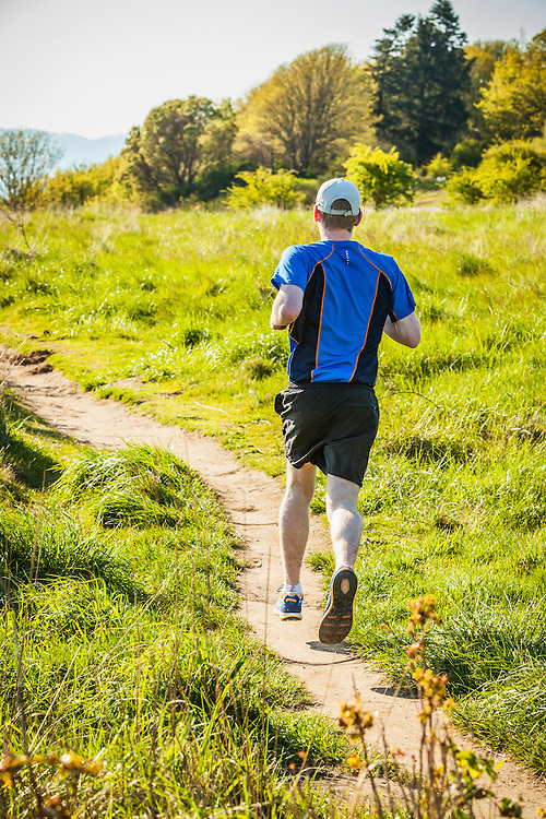A young man running one of the trails in Seattle's Discovery Park. Seattle, Washington, USA.