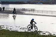flood of the Rhine on February 4th, 2021, child rides a bicycle through the water on the flooded bank of the Rhine in Deutz, Cologne, Germany.<br /> <br /> Hochwasser des Rheins am 4. Februar 2021, Kind faehrt mit Fahrrad durch das Wasser am ueberfluteten Rheinufer in Deutz, Koeln, Deutschland.