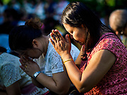 """17 MARCH 2018 - BANGKOK, THAILAND:  A woman prays during a """"sticky rice merit making"""" in Lumpini Park in Bangkok. Sticky rice merit making is a merit making in the Isan / Lao style, when people present small amounts of cooked sticky rice (also known as glutinous rice) to Buddhist monks. Isan is the northeast region of Thailand.     PHOTO BY JACK KURTZ"""