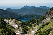 """Mowich Lake seen from Knapsack Pass trail, which is a steep """"social trail"""" in Mount Rainier National Park, Washington, USA. Caution: the unmaintained and unmarked Knapsack Pass trail exposes experienced hikers to slippery scree and steep snow (possibly icy), best hiked in late summer using a good GPS device, map, and trekking poles. The Spray Park–Knapsack Pass Loop is very rewarding but only recommended for experienced, well-equipped hikers."""