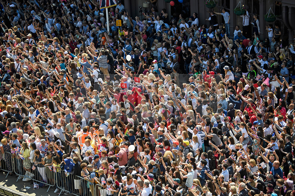 © Licensed to London News Pictures. 19/05/2018. London, UK. Members of the public line the streets to watch An open top carriage carrying Prince Harry and Meghan Markles make its way through Windsor. Guests arrive at The wedding of Prince Harry, The Duke of Sussex to Meghan Markle, The Duchess of Sussex, at St George's Chapel in Windsor. Photo credit: Ben Cawthra/LNP