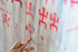 April 15, 2018 - Agartala, Tripura, India - Devotees draw Swastik Sign, (The Holy Sign), in a wall of a temple for the good of the  family on the occasion of Poila Boishaak, the Bengali new year at Agartala. (Credit Image: © Abhisek Saha/Pacific Press via ZUMA Wire)