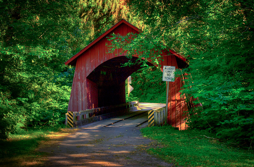A covered bridge in Yachats, Oregon in dappled late afternoon light.