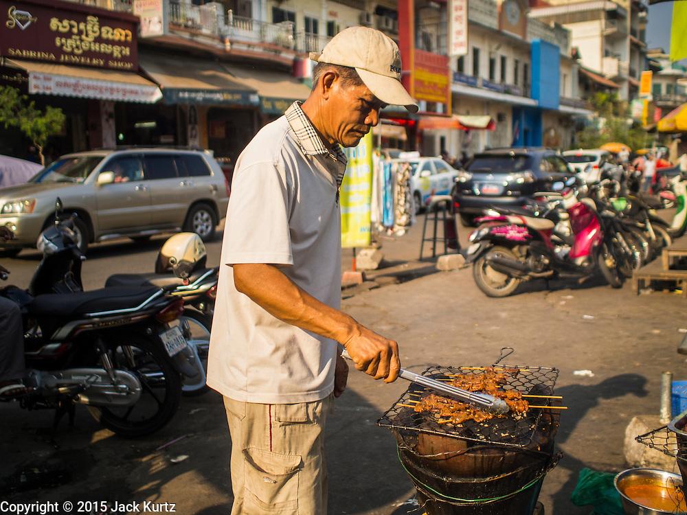 25 FEBRUARY 2015 - PHNOM PENH, CAMBODIA: A street food vendor grills pork sticks, called satay, in a market in Phnom Penh.      PHOTO BY JACK KURTZ
