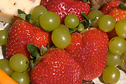 Close up photograph of strawberries, green grapes and cheese on a serving board