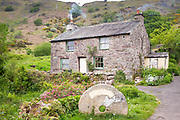 Quaint cottage with smoke coming out of chimney at Boot in Eskdale in the Lake District, Cumbria, England
