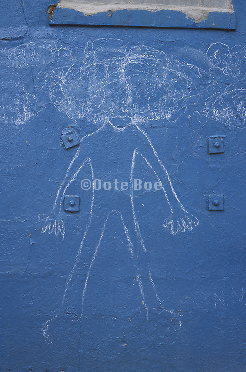 Chalk graffiti drawing on a blue wall
