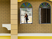 16 OCTOBER 2014 - BANGKOK, THAILAND: A construction worker seen through the window of a section of the remodeled Flower Market, Pak Khlong Talat, in Bangkok.    PHOTO BY JACK KURTZ