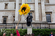 Beneath the statue of King James II as Roman Emperor, a tour guide leader carries a sunflower for his group to follow, passing the National Portrait Gallery in Trafalgar Square on 2nd May 2019, in London, England.