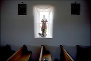 A statue of San Juan Neponuceno sits in a sunny afternoon window of the adobe walls inside the community church, which was built in the 1700s. San Juan Neponuceno is the patron saint of the community.
