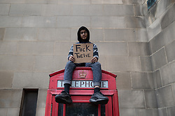 "© Licensed to London News Pictures. 07/06/2020. Manchester, UK. A boy sits on top of a telephone box with a sign that reads "" Fuck twelve "" . A Black Lives Matter demonstration against police violence is held in Manchester City Centre . Ongoing protests have and are being held in Manchester and around the world , after George Floyd was killed whilst being restrained by police in Minneapolis on 25th May 2020 . Photo credit: Joel Goodman/LNP"