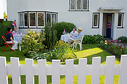 As the Coronavirus lockdown continues over the May Bank Holiday, the nation commemorates the 75th anniversary of VE Day Victory in Europe Day, the day that Germany officially surrendered in 1945 and in Dulwich, neighbours and residents emerge from their homes to party while still observing social distancing rules. Neighboursing friends take tea in their front garden, separated by shrubs, on 8th May 2020, in London, England.