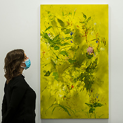 """© Licensed to London News Pictures. 03/12/2020. LONDON, UK. A staff member poses with """"Breathing Room, Flowers for Frank Bramblett"""", 2015.  Preview of """"Jennifer Packer: The Eye Is Not Satisfied With Seeing"""" at the Serpentine Gallery.  It is the American artist's first exhibition in a European institution and includes paintings and drawings from the past decade alongside recent works.  The exhibition opens to the public on 5 December. Photo credit: Stephen Chung/LNP"""
