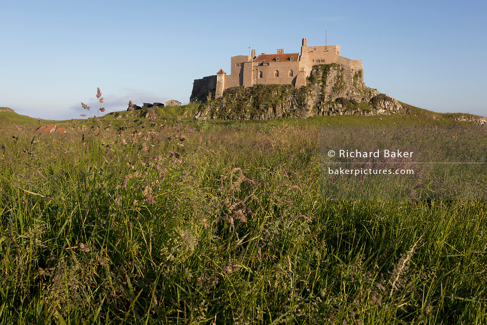 Lindisfarne Castle on Holy Island, on 27th June 2019, on Lindisfarne Island, Northumberland, England. The Holy Island of Lindisfarne, also known simply as Holy Island, is an island off the northeast coast of England. Holy Island has a recorded history from the 6th century AD; it was an important centre of Celtic and Anglo-saxon Christianity. After the Viking invasions and the Norman conquest of England, a priory was reestablished.