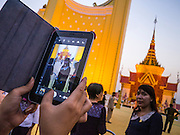 """31 JANUARY 2013 - PHNOM PENH, CAMBODIA: A person takes a photo of Norodom Sihanouk's crematorium at the National Museum in Phnom Penh. Norodom Sihanouk (31 October 1922- 15 October 2012) was the King of Cambodia from 1941 to 1955 and again from 1993 to 2004. He was the effective ruler of Cambodia from 1953 to 1970. After his second abdication in 2004, he was given the honorific of """"The King-Father of Cambodia."""" Sihanouk served two terms as king, two as sovereign prince, one as president, two as prime minister, as well as numerous positions as leader of various governments-in-exile. He served as puppet head of state for the Khmer Rouge government in 1975-1976. Most of these positions were only honorific, including the last position as constitutional king of Cambodia. Sihanouk's actual period of effective rule over Cambodia was from 9 November 1953, when Cambodia gained its independence from France, until 18 March 1970, when General Lon Nol and the National Assembly deposed him. Upon his final abdication, the Cambodian throne council appointed Norodom Sihamoni, one of Sihanouk's sons, as the new king. Sihanouk died in Beijing, China, where he was receiving medical care, on Oct. 15, 2012. His funeral procession, which will wind through Phnom Penh is Friday, Feb.1 and his cremation is on Feb. 4, 2013. Over a million people are expected to attend the service.     PHOTO BY JACK KURTZ"""