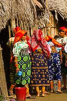 Kuna Indian women in native costume (with mola embrodery blouse) fetching water in the village on Crab Island (Carti Sugdup), San Blas Islands (Kuna Yala), Caribbean Sea, Panama