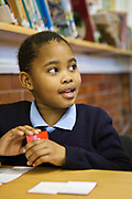A young African schoolgirl looks at her teacher to answer a question in a classroom in Prestwich Primary School, Green Point, Cape Town, South Africa.  She is using red flash cards as a tool to learn reading.
