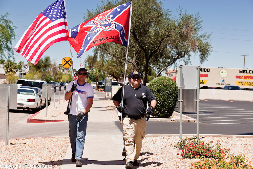 May 29 - PHOENIX, AZ: Supporters of Arizona SB1070 walk down a Phoenix street with American and Confederate flags. They were two of about five people who demonstrated in favor the bill while more than 30,000 people, supporters of immigrants' rights and opposed to Arizona SB1070, marched through central Phoenix to the Arizona State Capitol Saturday. SB1070 makes it an Arizona state crime to be in the US illegally and requires that immigrants carry papers with them at all times and present to law enforcement when asked to. Critics of the law say it will lead to racial profiling, harassment of Hispanics and usurps the federal role in immigration enforcement. Supporters of the law say it merely brings Arizona law into line with existing federal laws.  Photo by Jack Kurtz