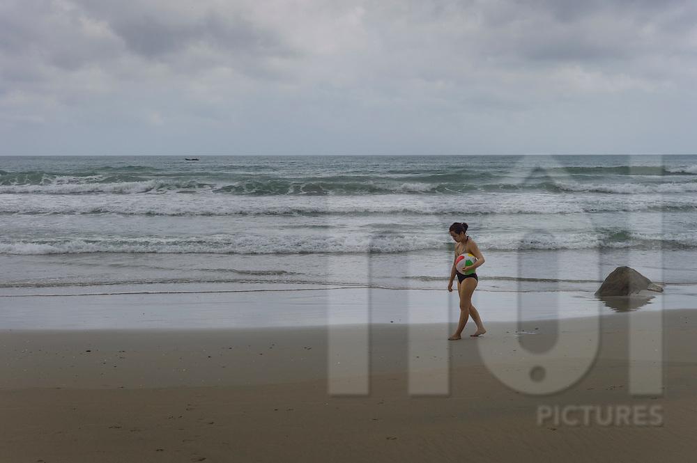A woman walks along the shore holding a beach ball under her arm, Jungle beach resort, Ninh Hoa District, Khanh Hoa Province, Vietnam, Southeast Asia