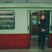 In the subway, just after the end of school. Young student are playing with their iphone, joking, dancing. The cars are coming from east Berlin. Le métro de Pyongyang, enterré à plus de 100 mètres sous terre. Les rames, rachetées au transports est-berlinois, sont bondées et désuettes mais impeccables. C'est un des seuls endroit où l'on peut cotoyer des nord Coréens. Certains préfèrent parfois changer de rame que de prendre le risque d'être vu avec un occidental.