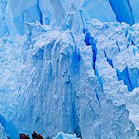 Tourist cruise in a zodiak raft under towering glacial seracs that calve into Paradise Bay, Antarctica.