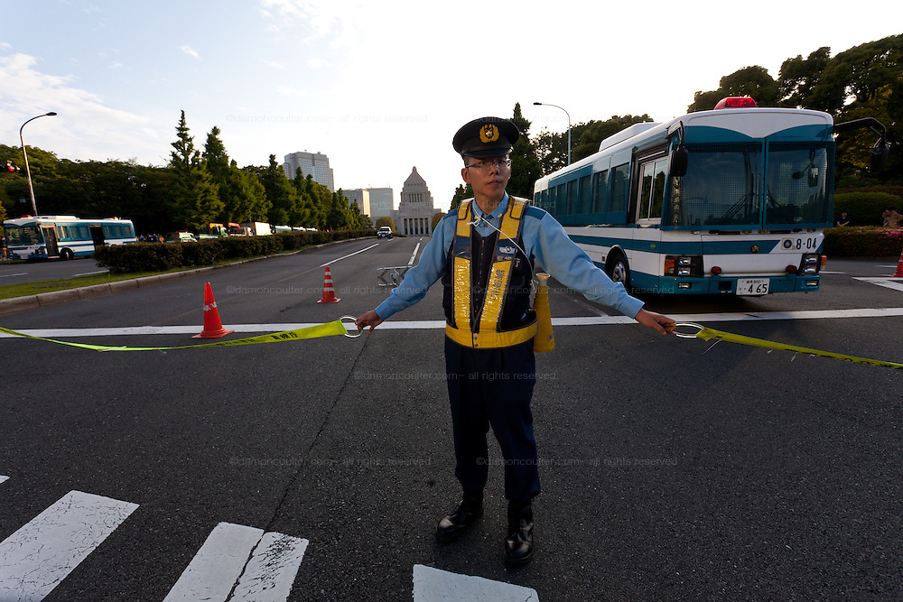 A policeman seals the approach road to the National Diet Building during an anti nuclear protest. Tokyo, Japan Sunday June 2nd 2013
