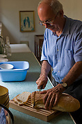 Riccardo Casagrande, monk brother priest, cuts bread as he prepares for lunch at the San Marcello al Corso Church in Rome, Italy, near the Spanish Steps. (Riccardo Casagrande is featured in the book What I Eat: Around the World in 80 Diets.) Casagrande is in charge of the kitchen, garden, and wine cellar for the brotherhood. MODEL RELEASED.