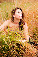 Beautiful woman poses in golden grass on an overcast day.