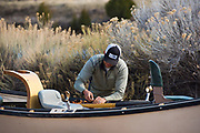 Utah Fish Chaser Jordan buttons up the drift boat at the take-out in preparation for the next day.