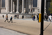 Pedestrians dash across a road crossing point on a red light below the pillars of St Paul's Cathedral in Central London.