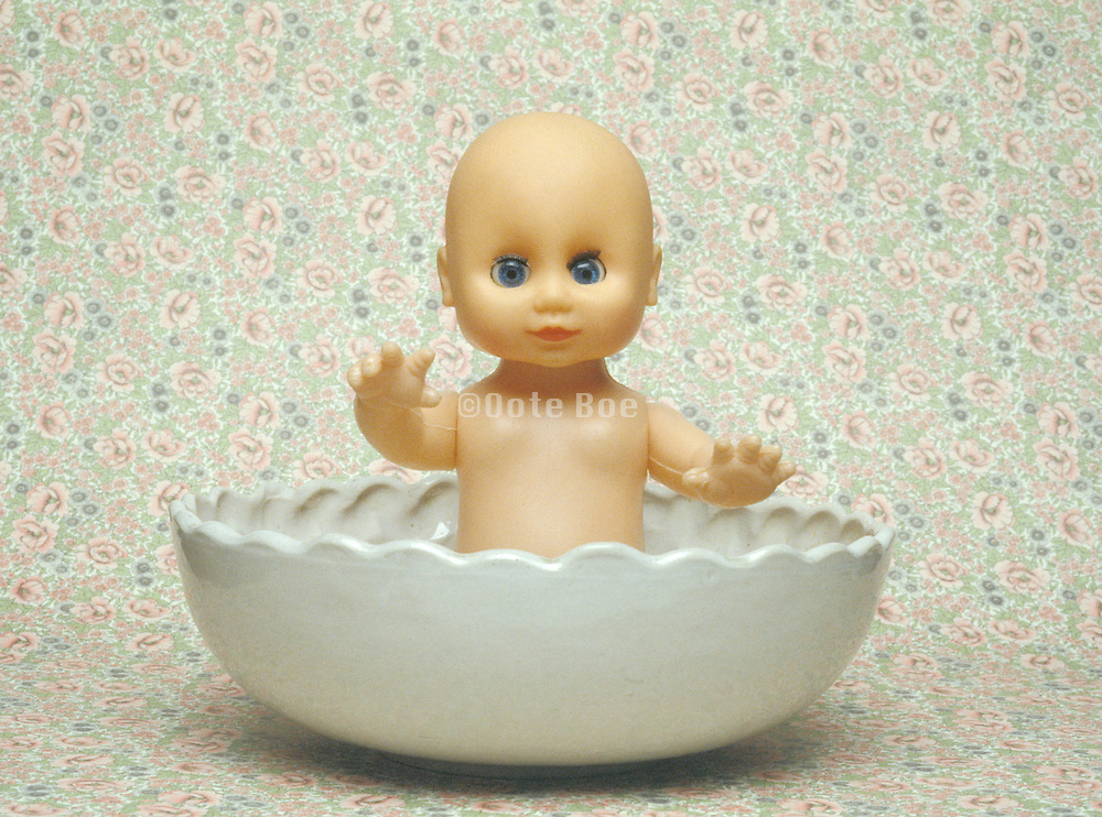 doll sitting in ceramic bowl with floral print background