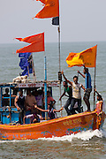 Young Indian men on boat trip celebrating Hindu Holi festival of colours at Nariman Point, Mumbai, formerly Bombay, India