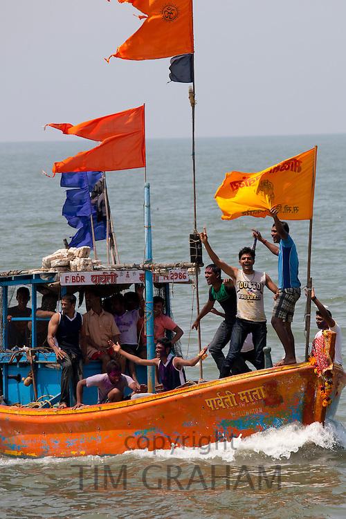 Young Indian men on boat trip celebrating Hindu Holi festival of colours at Nariman Point, Mumbai, formerly Bombay, India