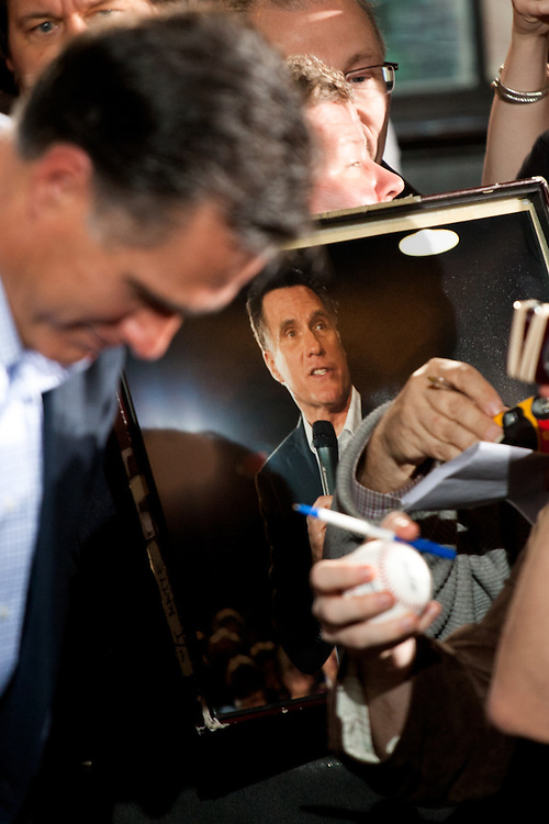 A Romney supporter holds a photograph of the governor in the crowds of people after his speech.