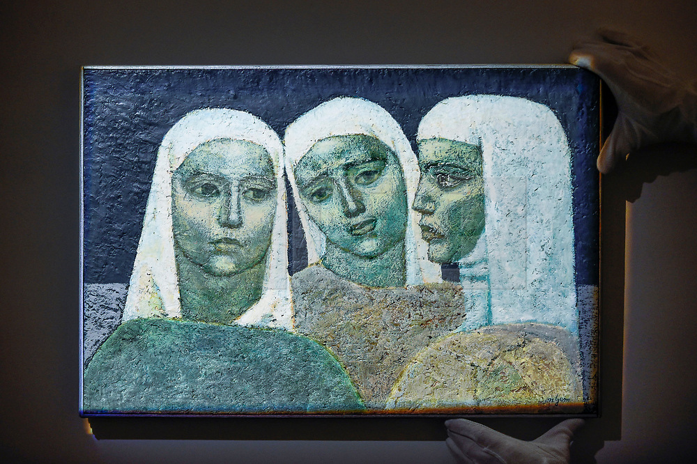 """© Licensed to London News Pictures. 18/10/2019. LONDON, UK. A technician presents """"Three Sisters-in-law"""" by Nuri Iyem (Est. GBP5,000-7,000).  Preview of Islamic, Indian and Middle Eastern art to be auctioned at Sotheby's, New Bond Street, on 22 and 23 October.  Photo credit: Stephen Chung/LNP"""