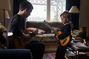 A 16 year-old teenager and his 4 year-old cousin face each other to play acoustic guitar together in the family living room. Playing their musical instruments, the older boy knows how to pluck the strings to make a pleasant sound while the younger lad simply brushes his fingers across the strings to make a noise. But music brings their age gap closer as they perform a pretend concert in front of family elders.