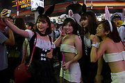 Japanese girls in costumes take a selfie as police try to keep people moving during the Halloween celebrations Shibuya, Tokyo, Japan. Saturday October 27th 2018