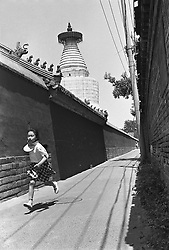 A girl running in a traditional hutong next to Buddhist temple in Bejing