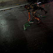 A revolutionary fighter collects pro-Gadhafi flags near a road block under a bypass in central Tripoli.