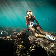 Female Freediver swimming in rays of light near Kailua Kona, Big Island, Hawaii.
