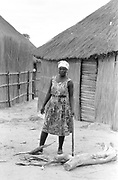 Woman holding axe in village, mean look