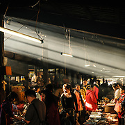 The morning sunlight catches the smoke as vendors at the morning market in Phonsavan in northeast Laos sell a wide range of freshly cooked food and local cuisine, including grilled sparrow, pork, chicken, insects, bamboo rats, and dog. The people of the region are predominantly of Hmong ethnicity.