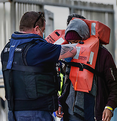 © Licensed to London News Pictures. 31/03/2021. Dover, UK. A Border Force officer helps a migrant remove his life jacket at Dover Harbour in Kent after crossing the English Channel. Home Secretary Priti Patel has pledged an overhaul of asylum seeker rules, with refugees having their claim assessed based on how they arrive in the UK. Photo credit: Stuart Brock/LNP
