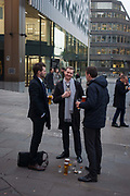 Young men enjoy work drinks outside a bar at Monument, their beers on the pavement, on 9th December 2016, in the City of London, England.