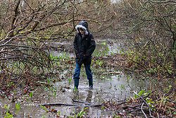 © Licensed to London News Pictures. 30/01/2021. London, UK. A boy walks through a flooded nature park in Hatton in Hounslow West London this morning as the Met Office issue weather warnings for heavy rain and flooding for large parts of England. The Met office has issued weather warnings for much of the UK this weekend for snow, torrential rain and flooding with disruption to travel as the stormy weather continues. Photo credit: Alex Lentati/LNP<br /> <br /> *Permission Granted*
